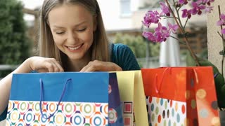 Girl checking her birthday presents and smiling to the camera, steadycam shot