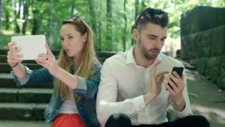 Girl doing photos on tablet while her boyfriend is using smartphone, steadycam s