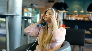 Girl in pink jumper wears headphones and starts listening music in the cafe