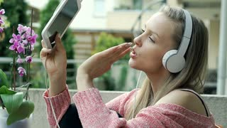Girl in pink sweater listening music and singing on patio, steadycam shot