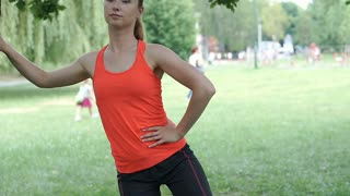 Girl leaning on the tree and exercising in the park, steadycam shot