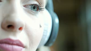 Girl listening music on headphones and crying because of hopelessness, steadycam