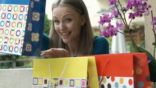 Girl looks excited with her shoppings and smiling to the camera, steadycam shot