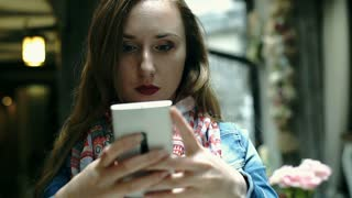 Girl looks irritated while texting with someone on smartphone