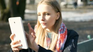Girl looks sad while browsing internet on tablet in the park