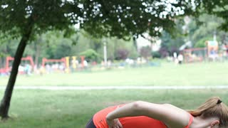 Girl looks tired while exercising in the park, steadycam shot