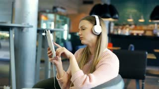 Girl looks worried while spinning on the swivel chair and listening music