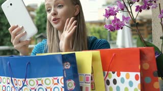 Girl showing her shoppings to a friend while having a videocall on tablet, stead