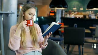 Girl smiling to the camera while reading book and drinking coffee from vintage m