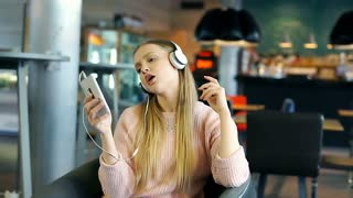 Girl spinning on swivel chair while listening music and singing