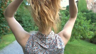 Girl standing back and touches her long hair, steadycam shot, slow motion shot a