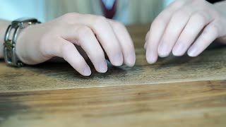 Girl tapping with her fingernails on wooden table because of irritation, steadyc