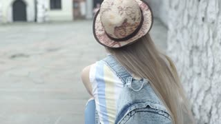 Girl with straw hat and backpack turns to the camera and smiling, steadycam shot