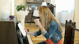 Girl writing music and learning it while playing the piano