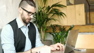 Handsome businessman working on new notebook and drinking coffee, steadycam shot