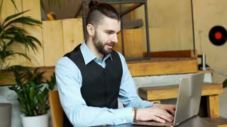 Handsome businessman working on notebook in the cafe and smiling to the camera,