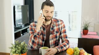 Handsome man drinking coffee in the flat and chatting on cellphone, steadycam sh