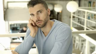 Handsome man in blue sweater doing worried look to the camera in the cafe, stead