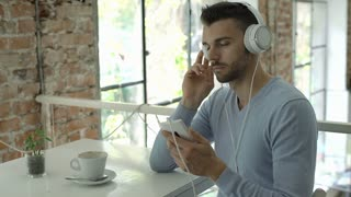 Handsome man in blue sweater listening music on headphones and smiling to the ca