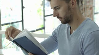 Handsome man in blue sweater sitting in the cafe and reading stupid book, steady