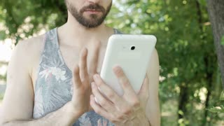 Handsome man in camis shirt browsing internet on tablet and receives good news,