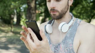 Handsome man in camis shirt checkes news on smartphone and looks unhappy, steady