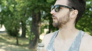 Handsome man in camis shirt drinking orange and laughing in the park, steadycam