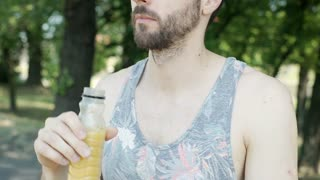 Handsome man in camis shirt drinking orange juice and smiling to the camera, ste