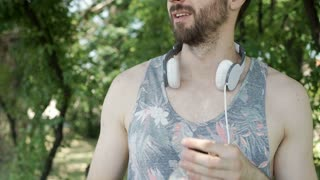 Handsome man in camis shirt drinking orange juice in the park and relaxing, stea
