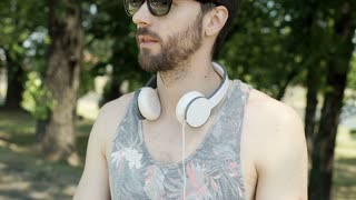 Handsome man in camis shirt puts on headphones and listening music, steadycam sh