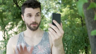 Handsome man in camis shirt standing in the park and having a videocall on smart