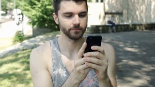 Handsome man in camis shirt texting messages on smartphone, steadycam shot