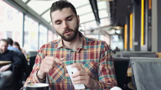 Handsome man in colorful shirt connects headphones to smartphone and plays music