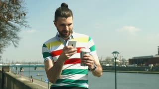 Handsome man in colorful shirt drinking coffee and using smartphone on boulevard