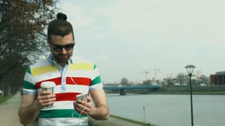 Handsome man in colorful shirt listening music while walking on boulevards, stea