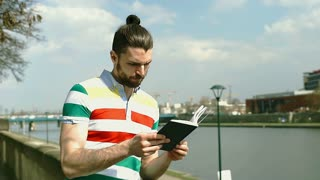 Handsome man in colorful shirt reading book on boulevards on sunny day