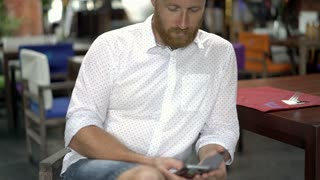 Handsome man in white shirt sitting in the restaurant and using smartphone, stea
