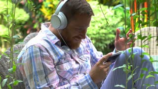 Handsome man laughing while watching funny video on smartphone