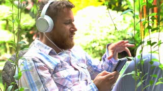 Handsome man listening music in his exotic garden and moving to the melody