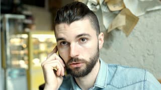 Handsome man looks pensive while speaking with someone on cellphone