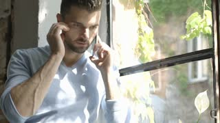 Handsome man looks worried while speaking on cellphone and sitting on window's s