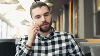 Handsome man looks worried while talking on cellphone in the cafe