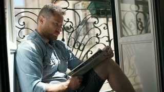 Handsome man reading newspaper and smiling to the camera, steadycam shot