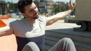 Handsome man relaxing in the city and stretching his muscles, steadycam shot