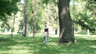 Handsome man riding on the bicycle in the park and smiling to the camera, steady
