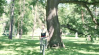 Handsome man riding on the bicycle in the park and talking to the camera, steady