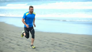 Handsome man running on the beach in the morning, slow motion shot at 240fps, st