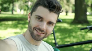 Handsome man sitting in the park and posing with face to the camera, steadycam s