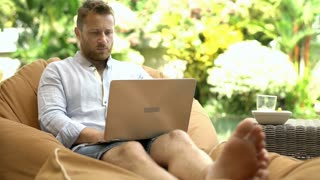 Handsome man sitting on the bean bag chair and finish using modern notebook