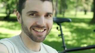 Handsome man smiling to the camera in the park and talking, steadycam shot